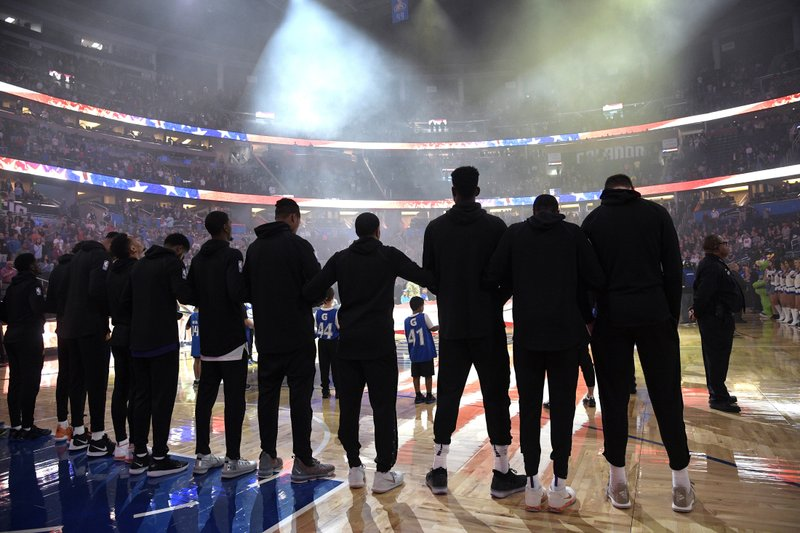 Phoenix Suns players lock arms during the singing of the national anthem before an NBA basketball game against the Orlando Magic on Wednesday, Dec. (AP Photo/Phelan M. Ebenhack)