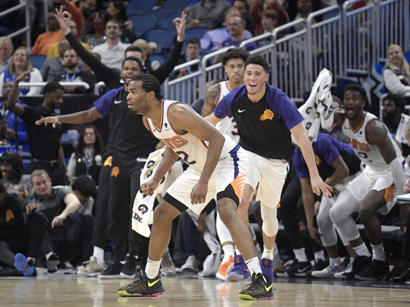 Phoenix Suns forward T.J. Warren, front, strikes a pose, as his teammates celebrate off the bench after his 3-pointer as time ran out in the first quarter of the team's NBA basketball game against the Orlando Magic Wednesday, Dec. (AP Photo/Phelan M. Ebenhack)