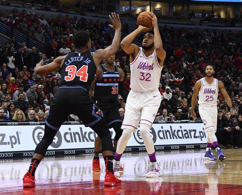 Minnesota Timberwolves center Karl-Anthony Towns (32) prepares to shoot over Chicago Bulls forward Wendell Carter Jr. (34) during the first half of an NBA basketball game Wednesday, Dec. 26, 2018, in Chicago. (AP Photo/Matt Marton)