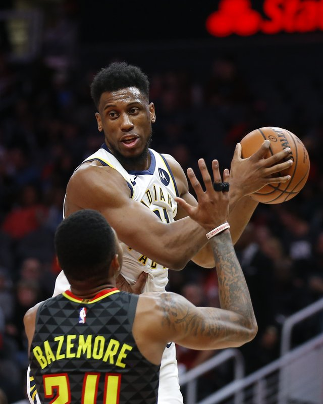 Indiana Pacers forward Thaddeus Young (21) is defended by Atlanta Hawks guard Kent Bazemore (24) during the second half of an NBA basketball game Wednesday, Dec. (AP Photo/Todd Kirkland)