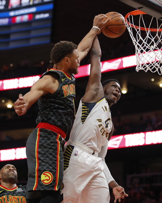 Indiana Pacers guard Victor Oladipo (4) has his shot deflected by Atlanta Hawks guard Justin Anderson (1) during the second half of an NBA basketball game Wednesday, Dec. (AP Photo/Todd Kirkland)