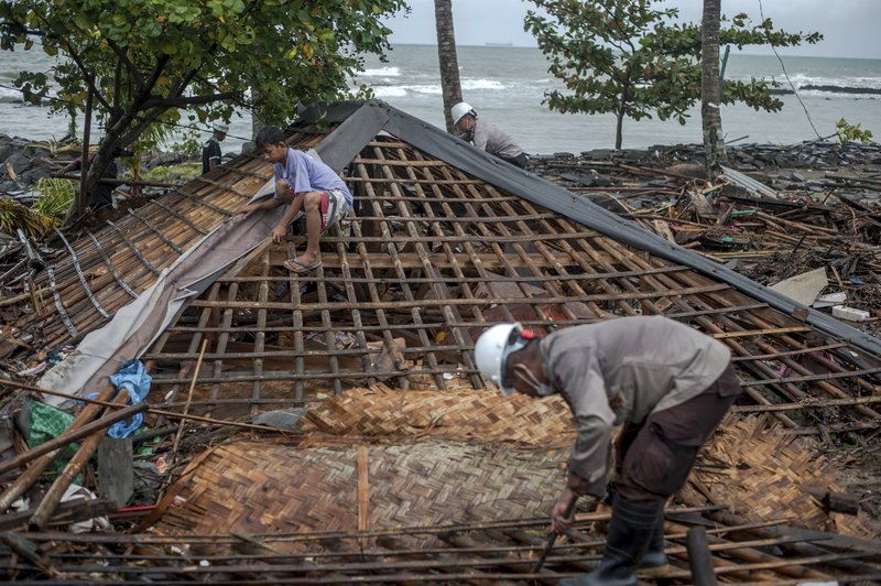Residents, assisted by police officers, clean up debris from the ruin of a house at a neighborhood affected by Saturday's tsunami in Carita, Indonesia, Wednesday, Dec. (AP Photo/Fauzy Chaniago)