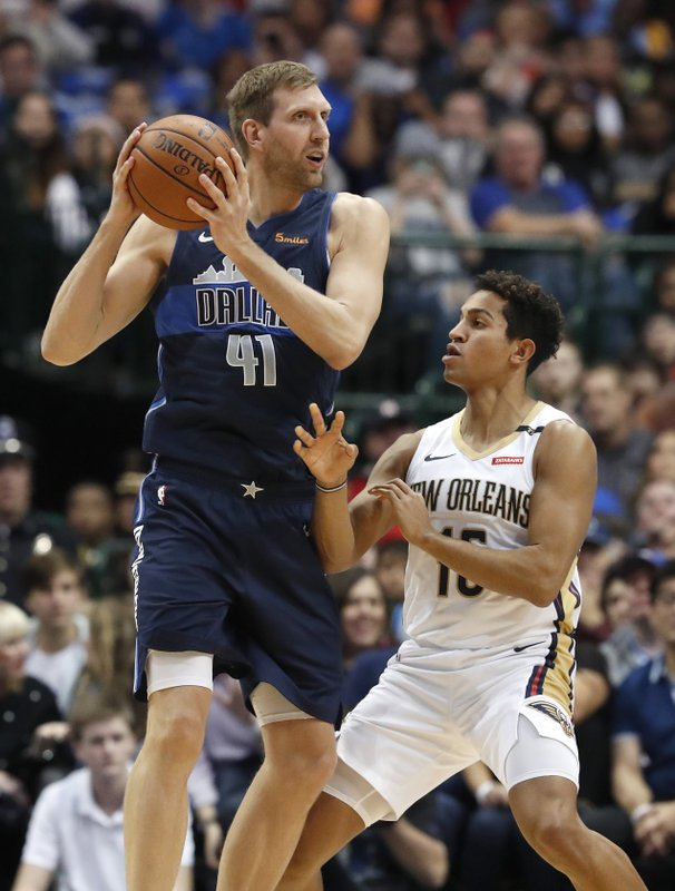 Dallas Mavericks forward Dirk Nowitzki (41) keeps the ball from New Orleans Pelicans guard Frank Jackson during the first half of an NBA basketball game in Dallas, Wednesday, Dec. (AP Photo/LM Otero)