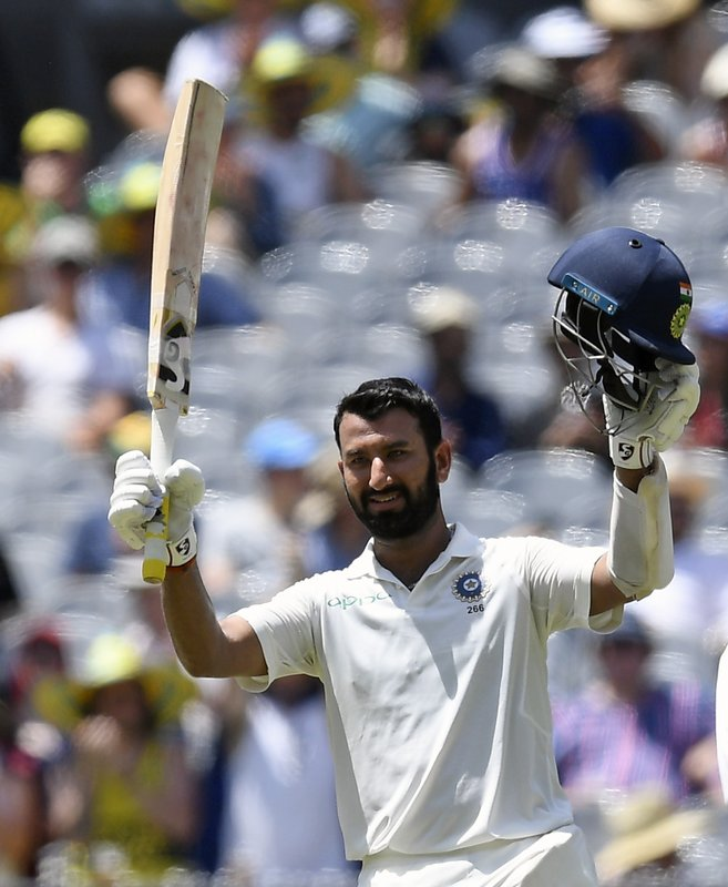 India's Cheteshwar Pujara celebrates scoring a century during play on day two of the third cricket test between India and Australia in Melbourne, Australia, Thursday, Dec. (AP Photo/Andy Brownbill)