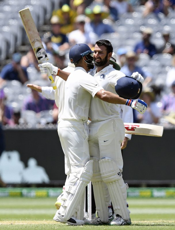India's Cheteshwar Pujara, right is congratulated by team mate Virat Kohli after scoring a century during play on day two of the third cricket test between India and Australia in Melbourne, Australia, Thursday, Dec. (AP Photo/Andy Brownbill)