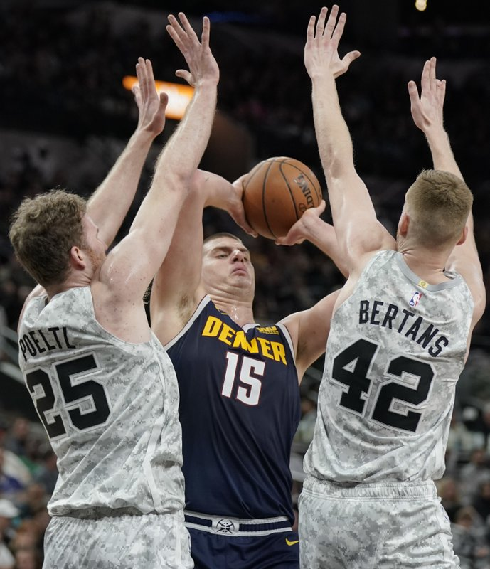 Denver Nuggets' Nikola Jokic (15) looks to pass the ball while San Antonio Spurs' Jakob Poeltl (25) and Davis Bertans defend during the first half of an NBA basketball game Wednesday, Dec. (AP Photo/Darren Abate)