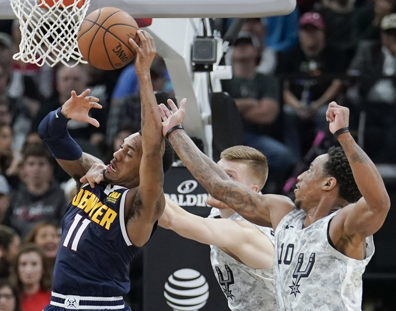 Denver Nuggets' Monte Morris, left, attempts to shoot against San Antonio Spurs' DeMar DeRozan, right, and Davis Bertans during the second half of an NBA basketball game Wednesday, Dec. (AP Photo/Darren Abate)