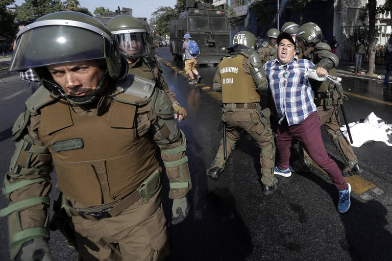 FILE - In this Jan. 16, 2018, file photo, a man is arrested during a protest against Pope Francis in Santiago, Chile. (AP Photo/Victor R. Caivano, File)