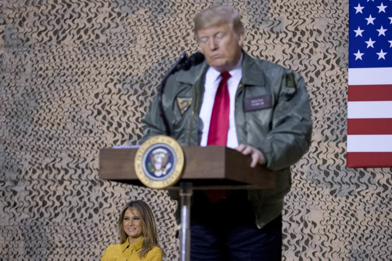 First lady Melania Trump, left, is seated on stage as President Donald Trump pauses as he speaks at a hanger rally at Al Asad Air Base, Iraq, Wednesday, Dec. (AP Photo/Andrew Harnik)