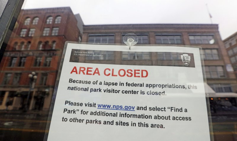 The tiny Klondike Gold Rush National Historical Park in Seattle's historic Pioneer Square neighborhood is posted with a closed sign as part of the federal government shutdown Wednesday, Dec. (AP Photo/Elaine Thompson)