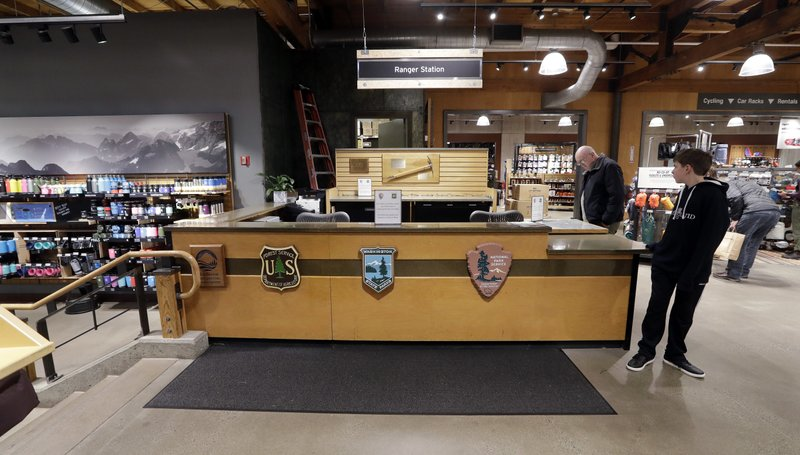 REI Co-op customers stand near an unstaffed ranger station kiosk, closed as part of the federal government shutdown, inside the flagship store Wednesday, Dec. (AP Photo/Elaine Thompson)