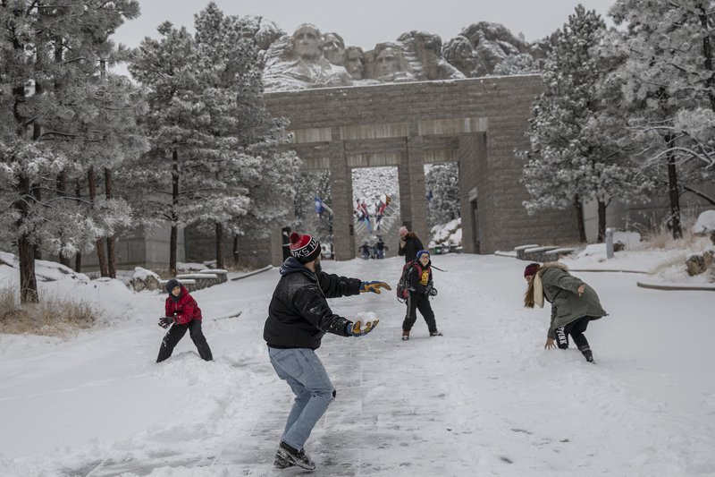 Nestor Marquez prepares to throw a snowball during a snowball fight with his children, from right, Jocelynn, 15, and Jon, 11, and family friend Anthony Zahn, left, 11, all of Chicago, at Mount Rushmore National Memorial near Keystone, S. (Ryan Hermens/Rapid City Journal via AP)