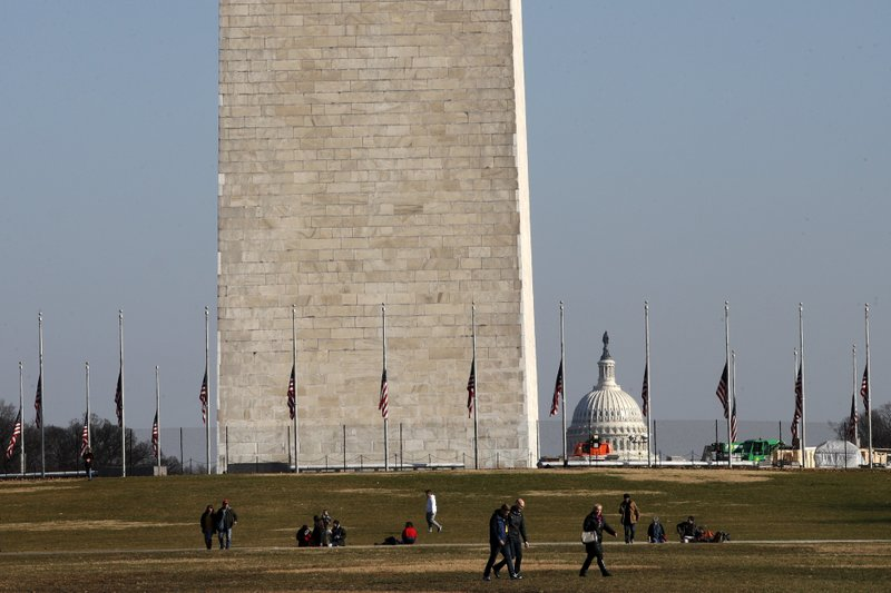 People walk near the Washington Monument, with the U.S. Capitol in the background, Wednesday, Dec. 26, 2018, as the partial government shutdown continues in Washington. (AP Photo/Jacquelyn Martin)
