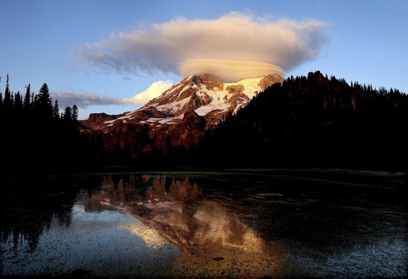 FILE - In this September 2012 file photo, a cloud hovers over Mount Rainier at sunset in a view from Klapatche Park Camp at Mount Rainier National Park, Wash. (Drew Perine/The News Tribune via AP, File)
