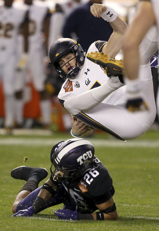 California quarterback Chase Garbers, top, gets upended by TCU safety Vernon Scott (26) during the first half of the Cheez-It Bowl NCAA college football game Wednesday, Dec. (AP Photo/Ross D. Franklin)