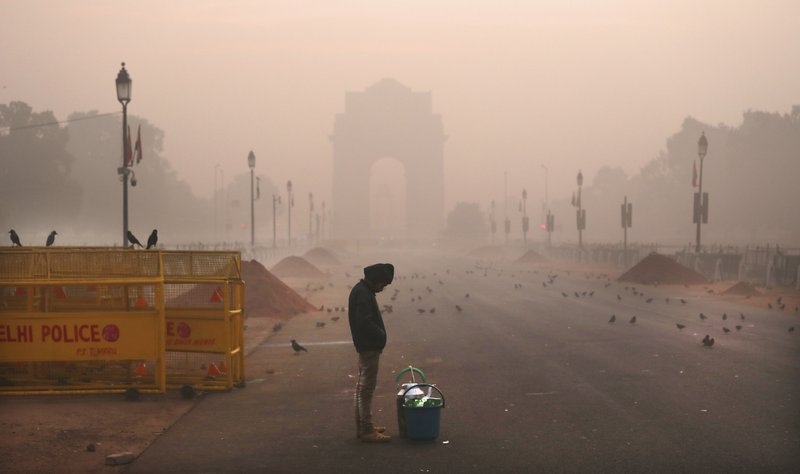 In this Wednesday, Dec. 26, 2018, photo, a boy selling tea awaits customers early morning amidst smog in New Delhi, India. (AP Photo/Manish Swarup)
