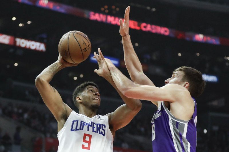 Los Angeles Clippers guard Tyrone Wallace, left, shoots over Sacramento Kings guard Bogdan Bogdanovic during the first half of an NBA basketball game in Los Angeles, Wednesday, Dec. (AP Photo/Chris Carlson)