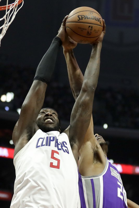 Los Angeles Clippers forward Montrezl Harrell (5) pulls a rebound away from Sacramento Kings forward Harry Giles during the second half of an NBA basketball game in Los Angeles, Wednesday, Dec. (AP Photo/Chris Carlson)