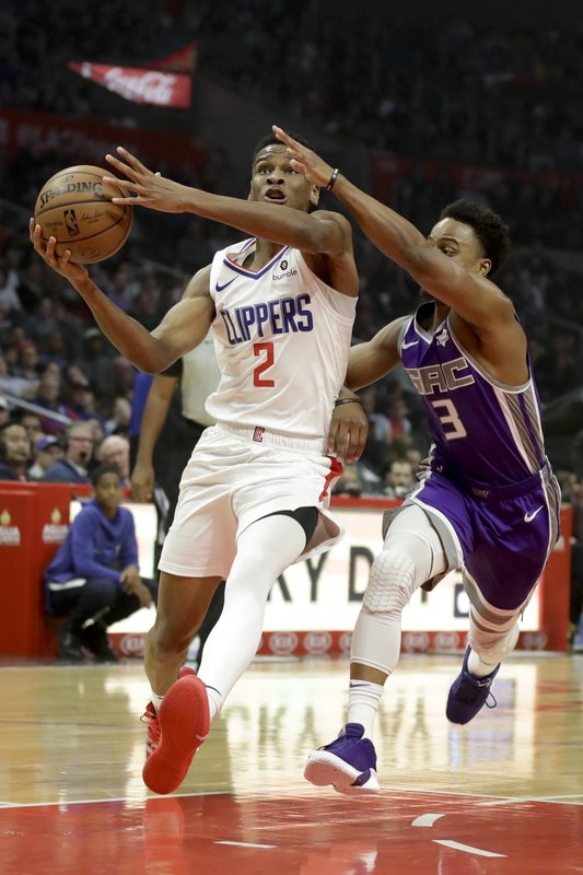 Los Angeles Clippers guard Shai Gilgeous-Alexander, left, drives to the basket around Sacramento Kings guard Yogi Ferrell during the first half of an NBA basketball game in Los Angeles, Wednesday, Dec. (AP Photo/Chris Carlson)