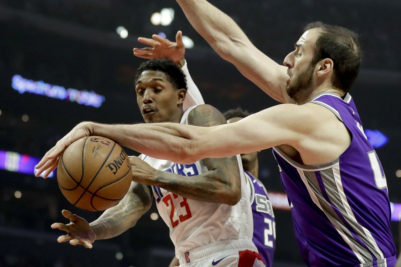 Sacramento Kings center Kosta Koufos, right, and blocks a shot by Los Angeles Clippers guard Lou Williams during the first half of an NBA basketball game in Los Angeles, Wednesday, Dec. (AP Photo/Chris Carlson)