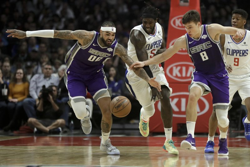 Sacramento Kings center Willie Cauley-Stein, left, and guard Bogdan Bogdanovic, right, take the ball away from Los Angeles Clippers forward Montrezl Harrell, middle, during the first half of an NBA basketball game in Los Angeles, Wednesday, Dec. (AP Photo/Chris Carlson)