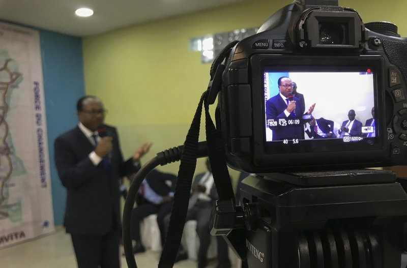 In this photo taken Tuesday, Dec. 11, 2018, presidential candidate NNoel Tshiani Muadimvita, seen on the screen of a media camera, addresses supporters at a campaign rally in Kinshasa, Congo. (AP Photo/Khaled Kazziha)