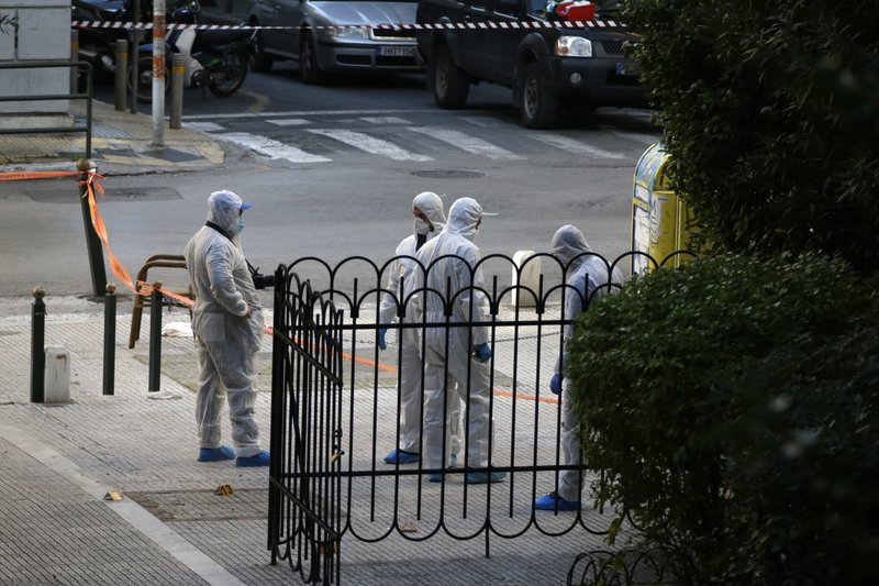 Greek forensic experts search at the scene after an explosion outside the Orthodox church of Agios Dionysios in the upscale Kolonaki area of Athens, Thursday, Dec. (AP Photo/Thanassis Stavrakis)