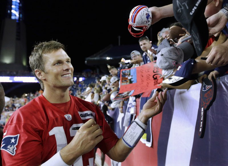 FILE - In this July 30, 2018 file photo, New England Patriots quarterback Tom Brady signs autographs for fans following an NFL football practice at Gillette Stadium, in Foxborough, Mass. (AP Photo/Steven Senne, File)