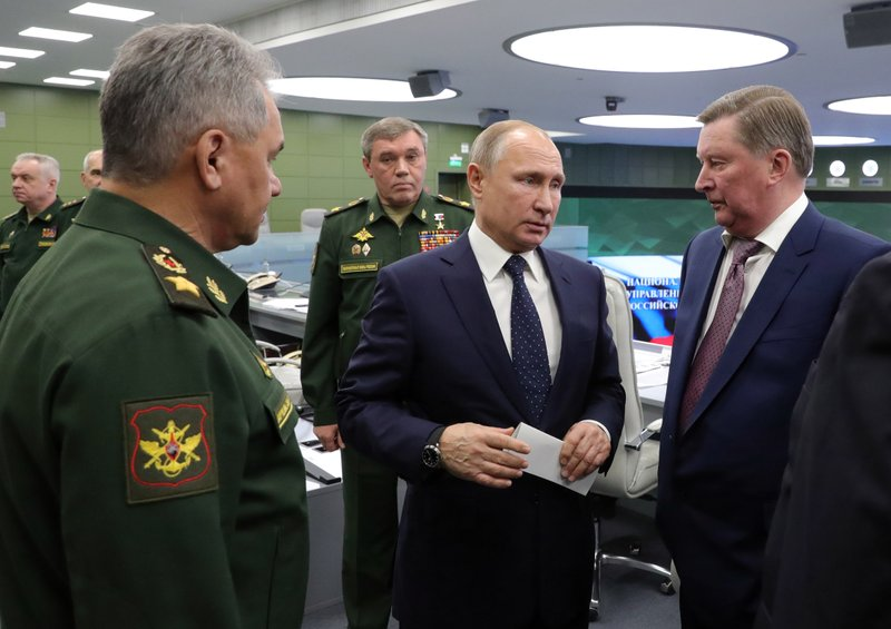 Russian Defense Minister Sergei Shoigu, left, Russian President Vladimir Putin, center, Chief of General Staff of Russia Valery Gerasimov, background center, and special representative on questions of ecology and transport, Sergei Ivanov, right, talk to each other as they come to oversee the test launch of the Avangard hypersonic glide vehicle from the Defense Ministry's control room in Moscow, Russia, Wednesday, Dec. (3,700 miles) away. (Mikhail Klimentyev, Sputnik, Kremlin Pool Photo via AP)
