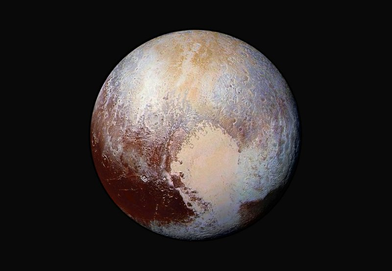 FILE - This image made available by NASA on Friday, July 24, 2015 shows a combination of images captured by the New Horizons spacecraft with enhanced colors to show differences in the composition and texture of Pluto's surface. (450,000 kilometers) away. (NASA/JHUAPL/SwRI via AP)