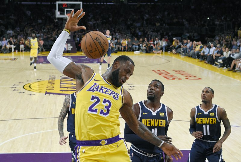 FILE - In this Tuesday, Oct. 2, 2018, file photo, Los Angeles Lakers forward LeBron James, left, follows through on a dunk as Denver Nuggets forward Paul Millsap, center, and guard Monte Morris watch during the first half of an NBA basketball game in Los Angeles. (AP Photo/Mark J. Terrill, File)