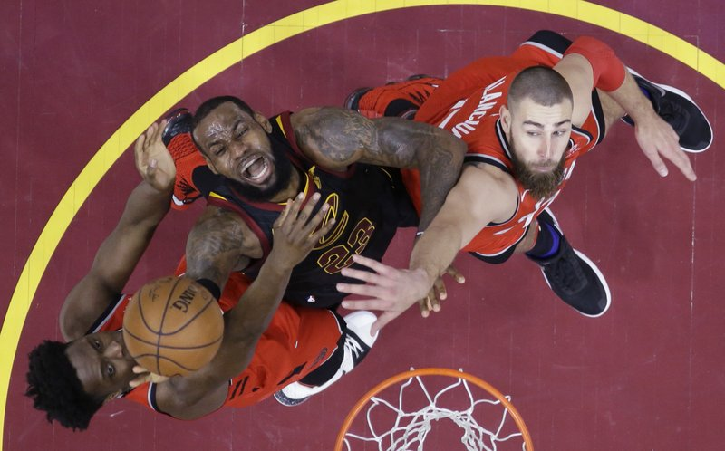 FILE - In this May 5, 2018, file photo, Cleveland Cavaliers' LeBron James (23) goes up for a shot between Toronto Raptors' OG Anunoby, left, and Jonas Valanciunas during the first half of Game 3 of an NBA basketball second-round playoff series in Cleveland. (AP Photo/Tony Dejak, File)