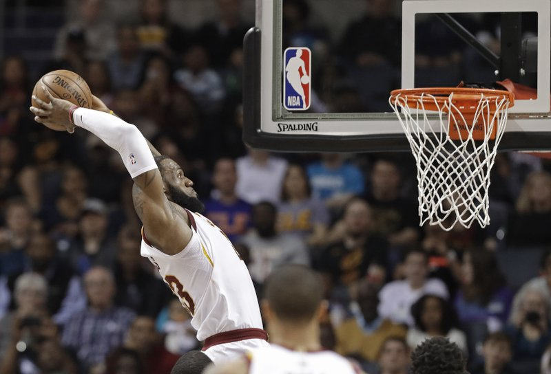 FILE - In this March 28, 2018, file photo, Cleveland Cavaliers' LeBron James goes up to dunk against the Charlotte Hornets during the first half of an NBA basketball game in Charlotte, N. (AP Photo/Chuck Burton, File)