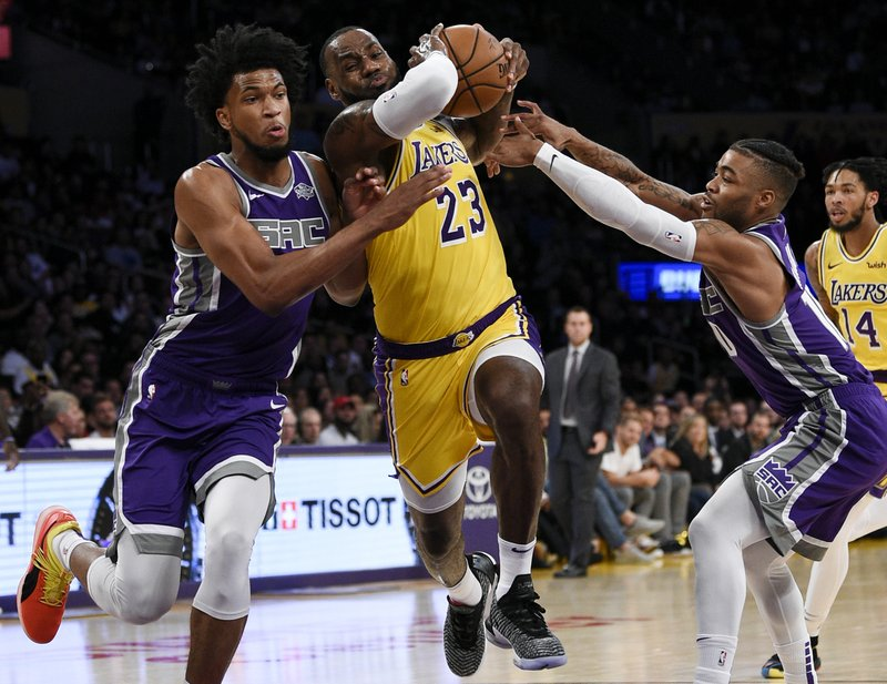 FILE - In this Oct. 4, 2018, file photo, Los Angeles Lakers forward LeBron James, center, drives between Sacramento Kings forward Marvin Bagley III, left, and guard Frank Mason III during the first half of an NBA preseason basketball game in Los Angeles. (AP Photo/Kelvin Kuo, File)