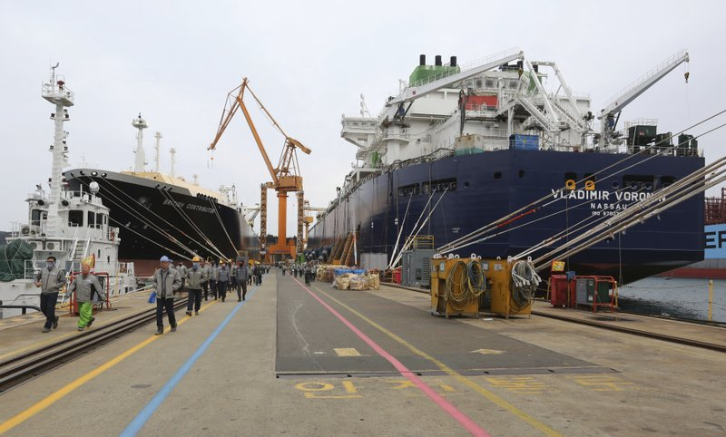 In this Friday, Dec. 7, 2018 photo, workers walk past large-sized liquefied natural gas (LNG) carriers under construction at the Daewoo Shipbuilding and Marine Engineering facility in Geoje Island, South Korea. (AP Photo/Ahn Young-joon)