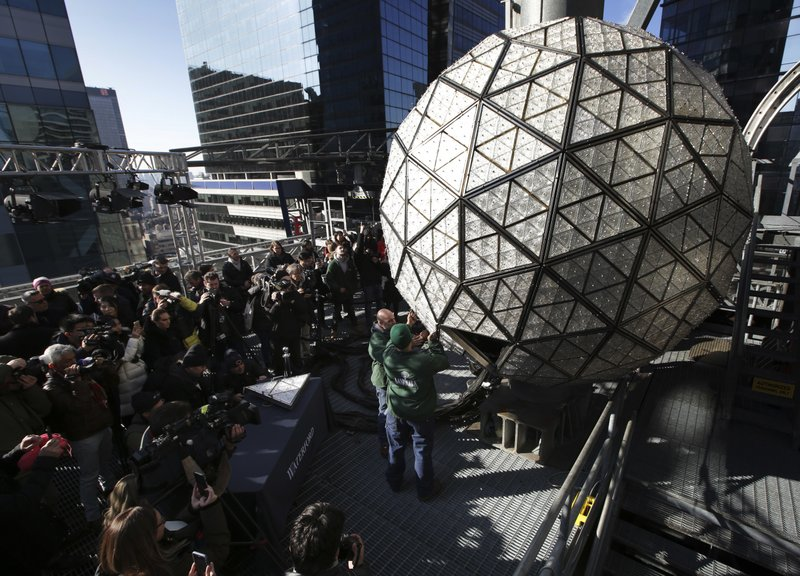 Media watch as workmen demonstrate the replacement of a panel on the New Year's Eve ball on top of a building in Times Square, New York, Thursday, Dec. (AP Photo/Seth Wenig)