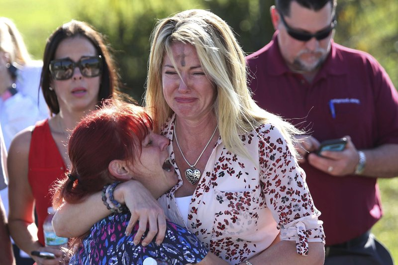 FILE- In this Feb. 14, 2018, file photo, parents wait for news after a reports of a shooting at Marjory Stoneman Douglas High School in Parkland, Fla. (AP Photo/Joel Auerbach, File)