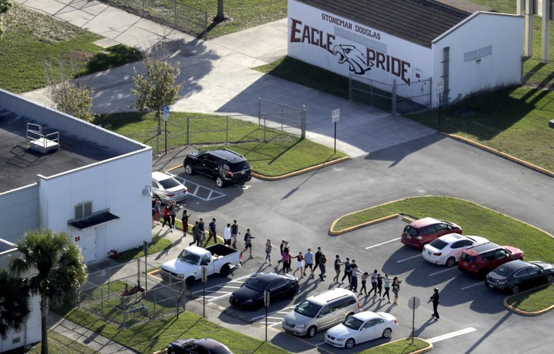 FILE - In this Feb. 14, 2018, file photo, students are evacuated by police from Marjory Stoneman Douglas High School in Parkland, Fla. (Mike Stocker/South Florida Sun-Sentinel via AP)