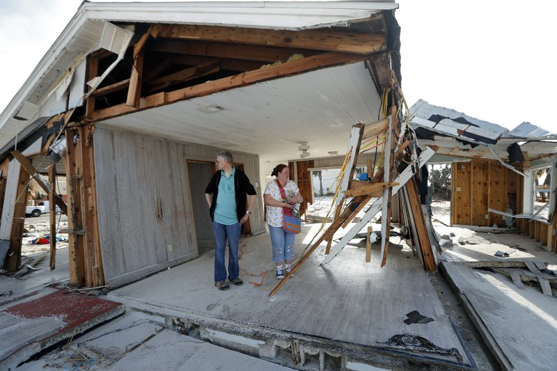FILE - In this Oct. 17, 2018, file photo, Lanie Eden and her husband Ron stand in the destroyed vacation home they rented every year as they look for their possessions in the aftermath of Hurricane Michael in Mexico Beach, Fla. (AP Photo/Gerald Herbert, File)