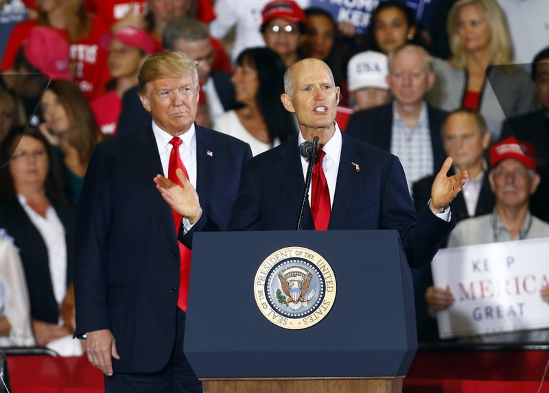FILE- In this Nov. 3, 2018, file photo President Donald Trump stands behind Florida Gov. Rick Scott as he speaks at a rally in Pensacola, Fla. (AP Photo/Butch Dill, File)