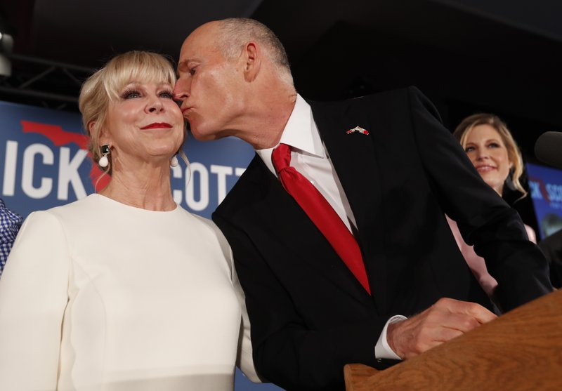 FILE- In this Nov. 7, 2018, file photo, Republican Senate candidate Rick Scott kisses his wife Ann as he speaks to supporters at an election watch party, in Naples, Fla. (AP Photo/Wilfredo Lee, File)