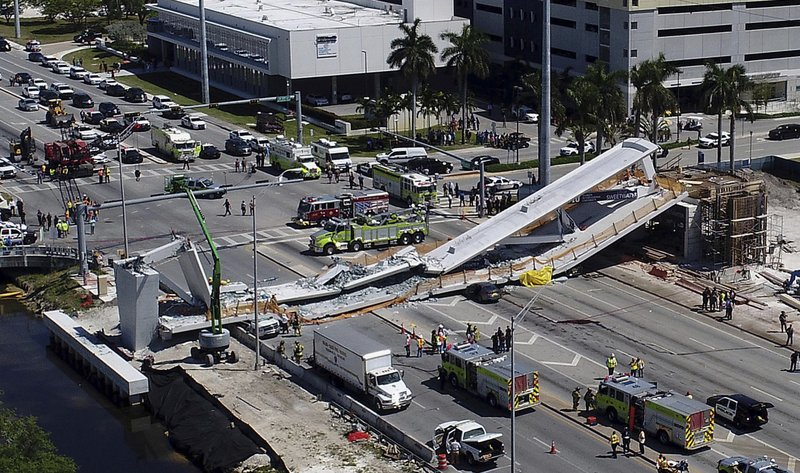 FILE- In this March 15, 2018, file photo, emergency personnel respond after a brand-new pedestrian bridge collapsed onto a highway at Florida International University in Miami. (Pedro Portal/Miami Herald via AP)