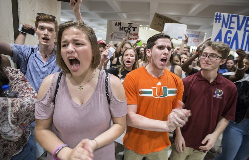 FILE- In this Feb. 21, 2018, file photo, students chant protest slogans outside the Florida House of Representatives chamber inside the Florida Capitol in Tallahassee, Fla. (AP Photo/Mark Wallheiser, File)