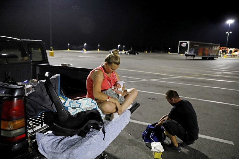 FILE - In this Oct. 15, 2018, file photo, Lorrainda Smith, sits with her two-day-old son, Luke, as she contemplates with her husband Wilmer Capps, right, sleeping in their truck in a parking lot after their home was damaged from Hurricane Michael and they were told a nearby shelter was closed, in Panama City, Fla. (AP Photo/David Goldman, File)