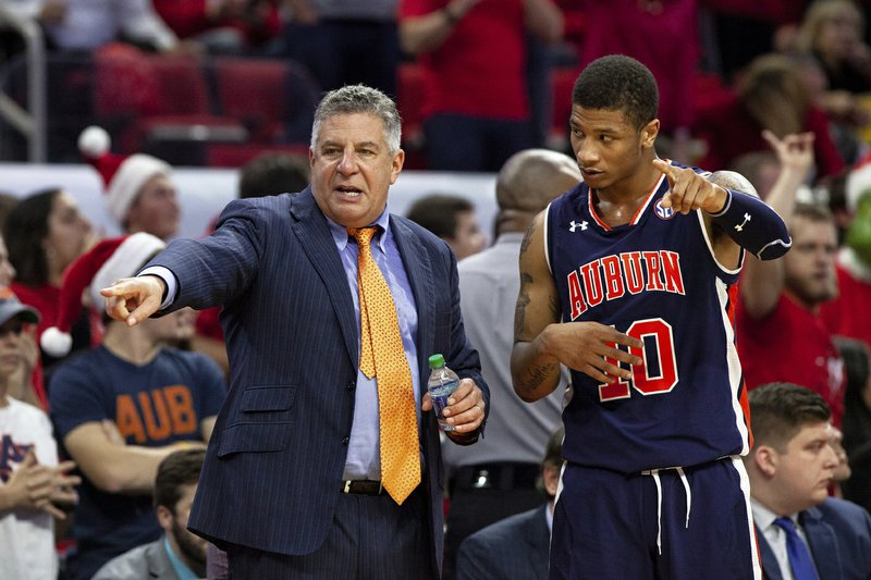 FILE - In this Dec. 19, 2018, file photo, Auburn head coach Bruce Pearl, left, speaks with Samir Doughty (10) during the second half of an NCAA college basketball game against North Carolina State in Raleigh, N. (AP Photo/Ben McKeown, File)