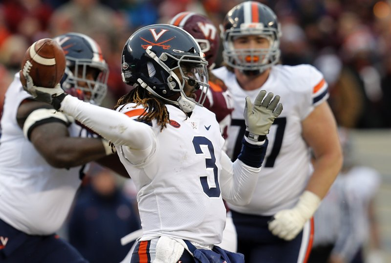 File-This Nov. 23, 2018, file photo shows Virginia quarterback Bryce Perkins (3) tossing a pass during the first half of an NCAA college football game against Virginia Tech in Blacksburg, Va. (AP Photo/Steve Helber, File)