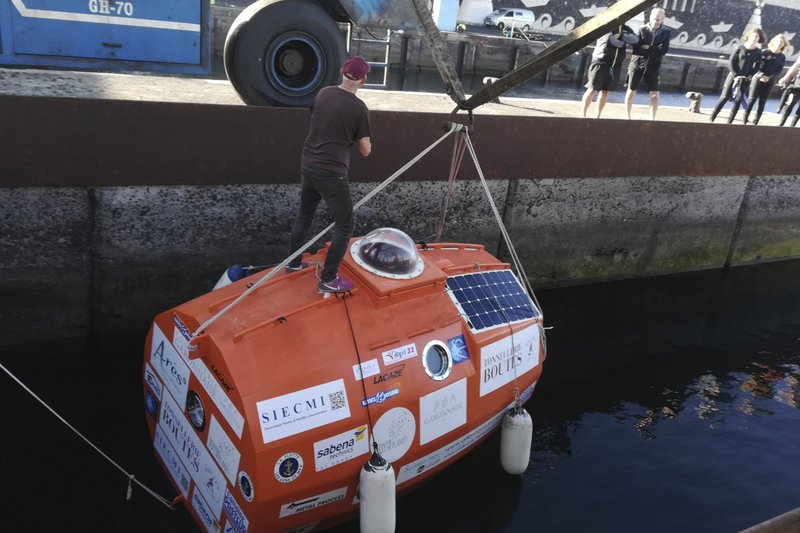 In this photograph taken Saturday Dec. 22, 2018, Frenchman Jean-Jacques Savin, 71-year-old, stands ontop of his 3-metre (10-foot) long, 2. (7-foot) wide resin-coated plywood capsule, which will use ocean currents alone to propel him across the sea. Savin set off from El Hierro in Spain's Canary Islands on Wednesday and is aiming to complete his 4,500-kilometre (2,800-mile) journey to the Caribbean in about three months. (Courtesy of Jean-Jacques Savin via AP)