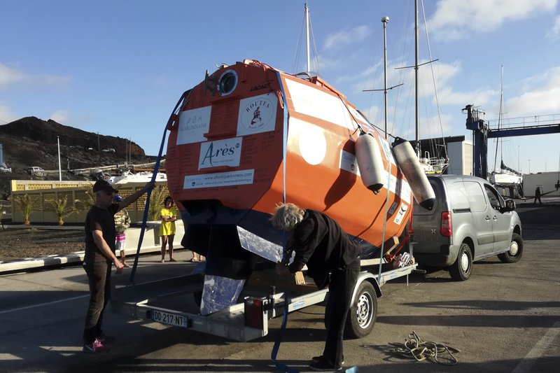 In this photograph taken Saturday Dec. 22, 2018, Frenchman Jean-Jacques Savin, 71-year-old, left, unloads his 3-metre (10-foot) long, 2. (7-foot) wide resin-coated plywood capsule, which will use ocean currents alone to propel him across the sea. Savin set off from El Hierro in Spain's Canary Islands on Wednesday and is aiming to complete his 4,500-kilometre (2,800-mile) journey to the Caribbean in about three months. (Courtesy of Jean-Jacques Savin via AP)