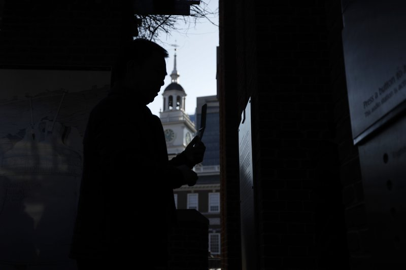A tourist to Independence National Historical Park takes a photograph through a window of the closed building housing the Liberty Bell, Wednesday, Dec. (AP Photo/Matt Slocum)