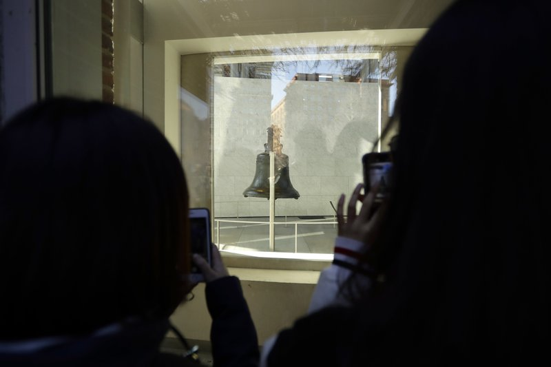 Tourists to Independence National Historical Park take photographs through a window of the closed building housing the Liberty Bell, Wednesday, Dec. (AP Photo/Matt Slocum)